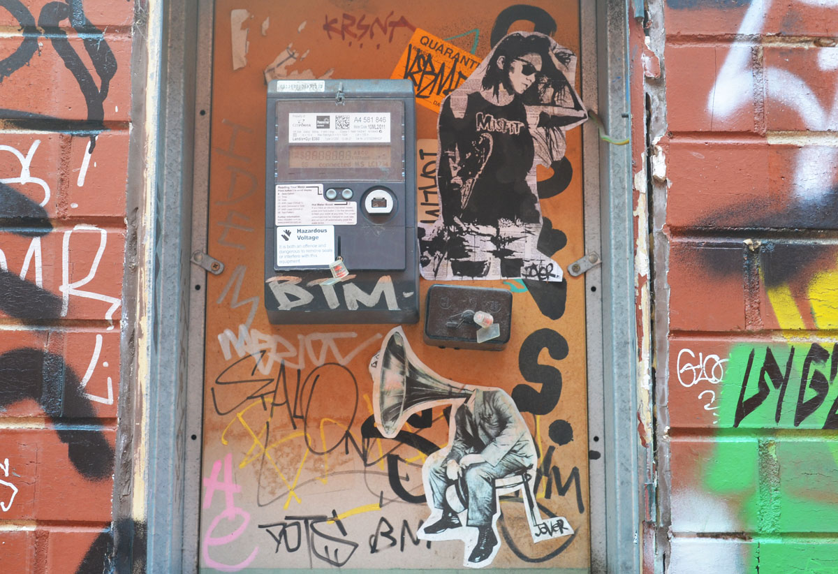 2 paste ups on a boarded up space on a wall. One is a person with a black t shirt with the word Misfits on it. The other is a man sitting on a stool but instead of a head he has the speaker part of an old gramophone