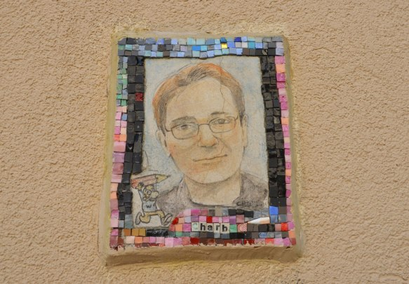 small portrait of a man on a wall.  Hand drawn head and shoulder shot, framed with tiny pieces of mosaic tile - Charb