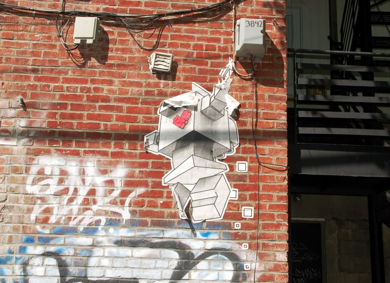 lovebot wheatpaste on a red brick wall with lots of hydro wires and cables