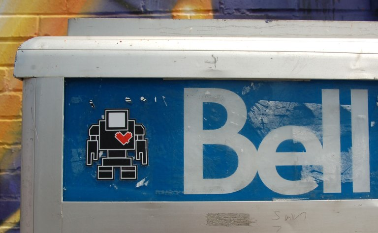 black lovebot sticker on the blue part of a Bell payphone
