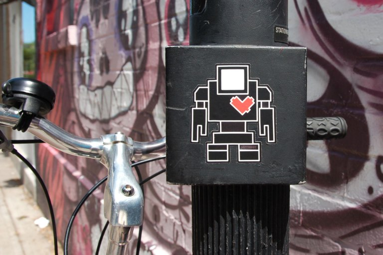 a black lovebot sticker on a black pole with a bike parked against that pole and a pink and purple mural of faces behind in the background