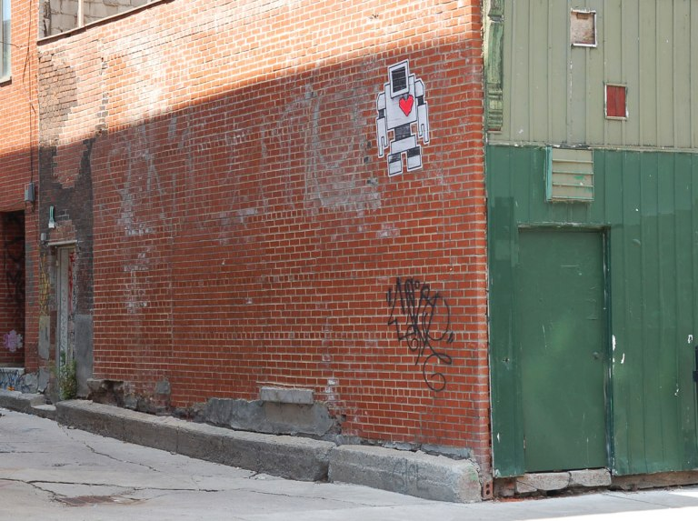 lovebot wheatpaste on a red brick wall on a building at the entrance to an alley