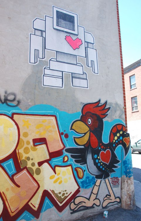 large wheatpaste paste up lovebot on a wall about a street art painting of a rooster who also has a heart on his body