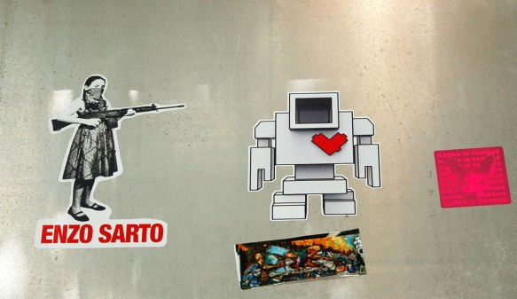 A light grey lovebot sticker beside a sticker of a girl with bandana over the lower part of his face and she is pointing her rifle at lovebot. The sticker of the girl is by Enzo Sarto and his name on it.
