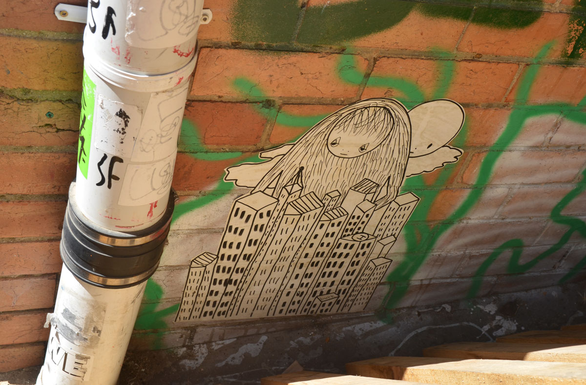 paste up of a black drawing on white, a girls head with very long hair looks over the top of a group of high rise buildings, cloud ans round sun behind her