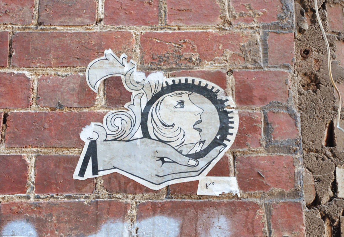 small black and white paste up of an open hand holding a round shape with a woman's head in profile in it.