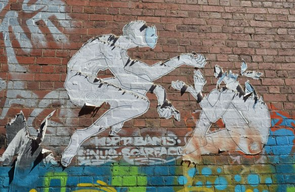 fraying paste up (large) of two people in blank masks. One is seated. The other is reaching out to him or her, on a brick wall in an alley