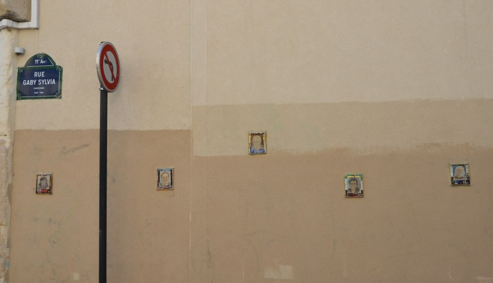 On a light brown stucco wall, sign for rue Gaby Sylvia, as well as 5 small portraits frames in tiny mosiac tiles