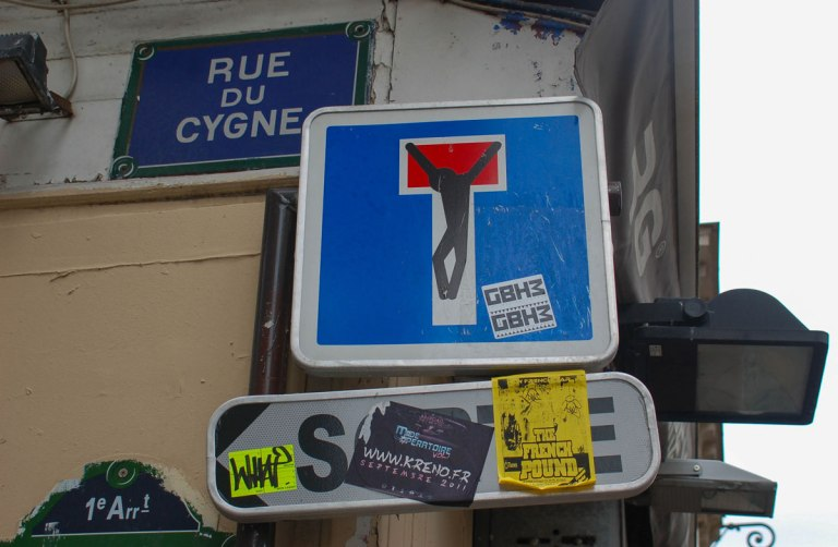 graffiti altered square dead end sign where the T has been made into a crucifixtion, black figure of Jesus on it.