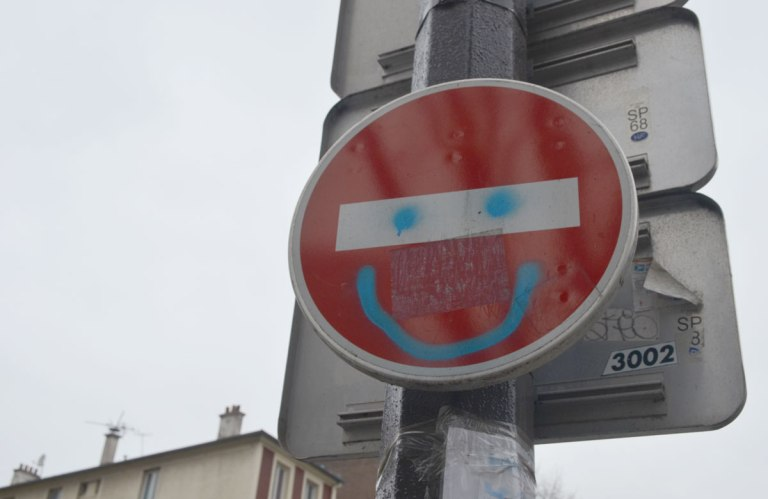 graffiti altered no entry sign, red circle with a white horizontal bar - added blue spray paint happy face