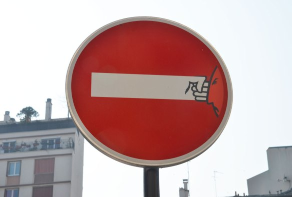 graffiti altered no entry sign, red circle with a white horizontal bar - added face on right side, lines on bar to make it look like an arm and a fist, punching the face