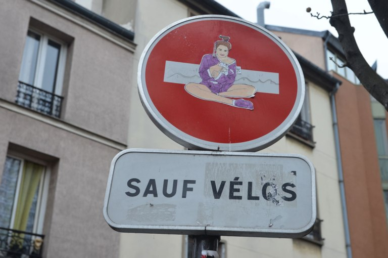 graffiti altered no entry sign, red circle with a white horizontal bar - added a pasteup of a woman sitting, wearing purple robe and slippers and holding a white stuffed bear