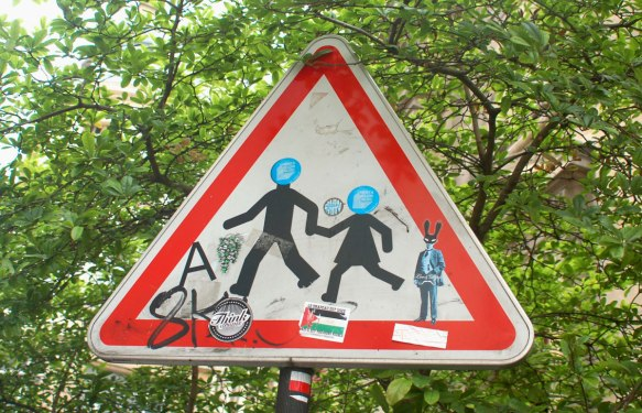 graffiti altered triangular sign of two kids running while holding hands, blue circle stickers have been put over their heads