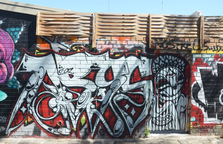 a large text street art piece in black, white and red, on a fence,