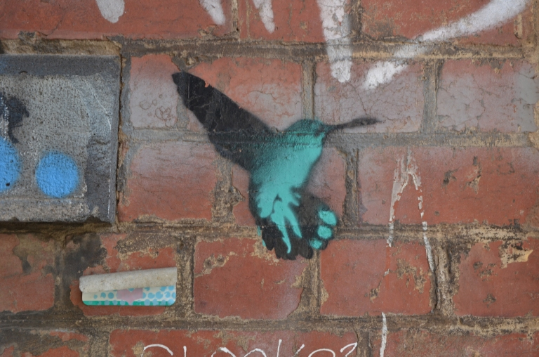 a stencil in teal and black of a hummingbird hovering