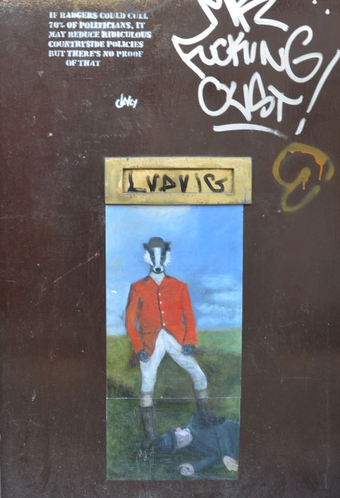 street art painting of a hunter in red jacket but with badger face standing over a person who is lying on the ground, one leg of badger person is on the other person's back