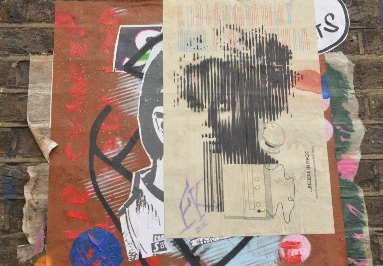 paste up graffiti of a woman's head with words