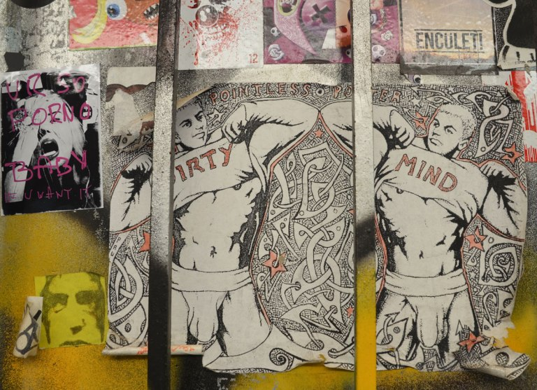 a group of pasteups on a wall. the largest one is of two guys in their underwear pulling their shirts up to reveal their stomachs and chest. One man has 'dirty' written on the shirt and the other has 'mind' written on his.
