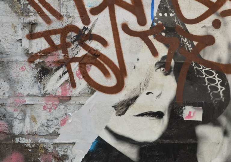 street art picture of a woman's face partially obscured by a brown tag