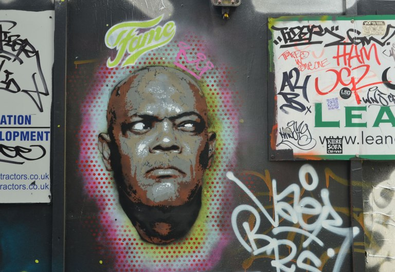 street art portrait of a black man's face, with the word fame written above it and a small pink crown drawn on the side of his head