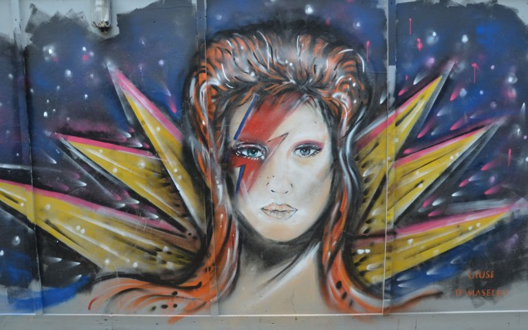 street art painting of a face with David Bowie like makeup and hair, although it doesn't really look like David Bowie