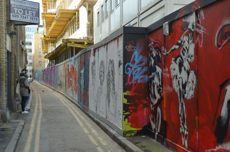 view of a narrow London Street with street art covered construction hoardings down one side, two young women taking photos of the hoardings on the left. New building under construction in the background.
