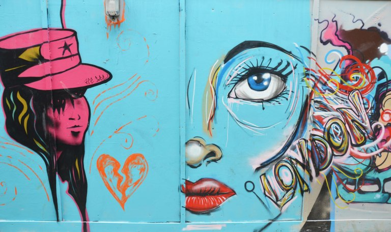 street art on construction hoardings on Blackall street in Hackney London. Light blue background. A young woman with hat all in dark pink, half of a woman's face (large) with bright red lips, blue eye and a multicoloured word London