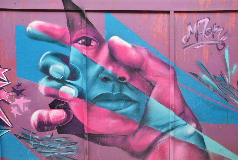 mural in pink and blue of a hand holding a face, by mask
