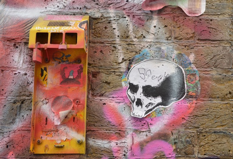 paste up of a skull, old mailbox broken, spray painted yellow and stickers on it