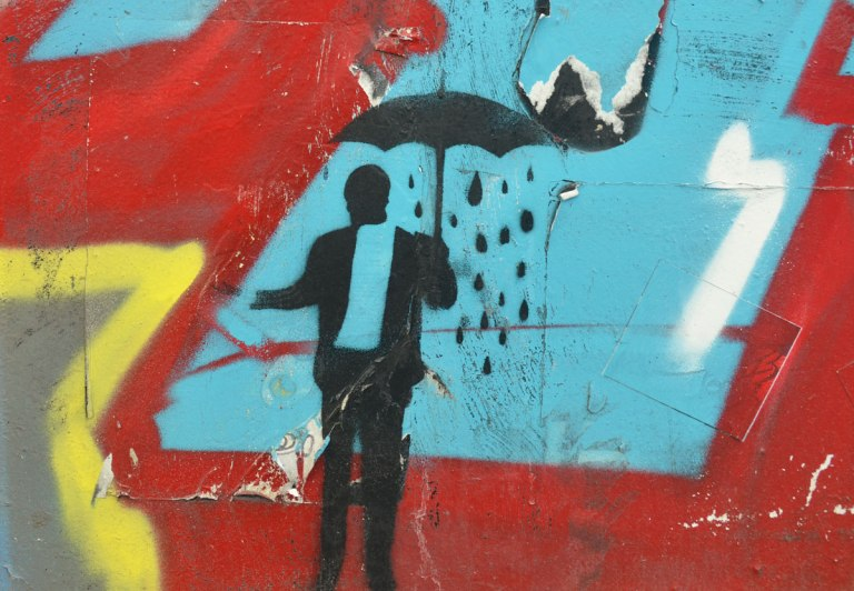 stencil of a man holding an umbrella, It is raining under the umbrella but not outside of it. Man is holding hand out to see if it is still raining.