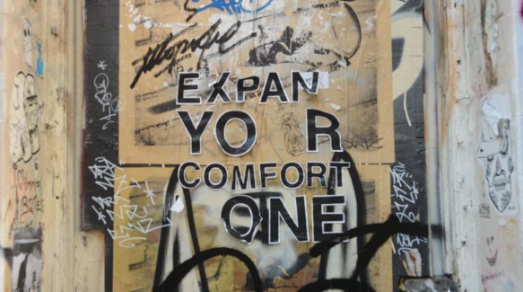 words on a graffiti covered wall that once said Expand your comfort zone, but some of the letters are missing and others are starting to peel.