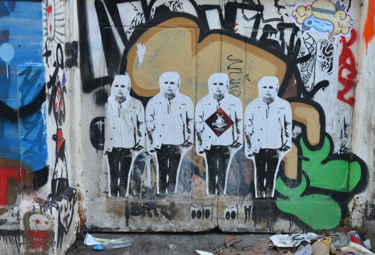 paste up of four men standing in a line, shoulder to shoulder, on a background of graffiti tags.