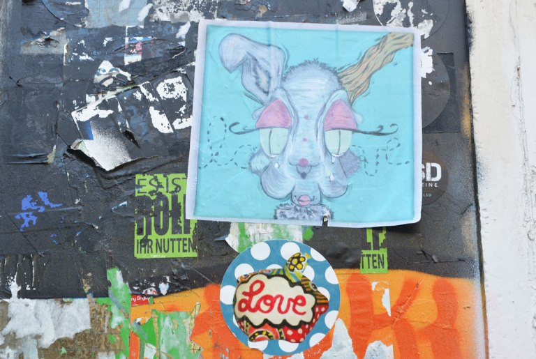 a square paste up of a rabbit's head and a circular paste up below it, white polka dots on blue with the word love written in cursive in the center.