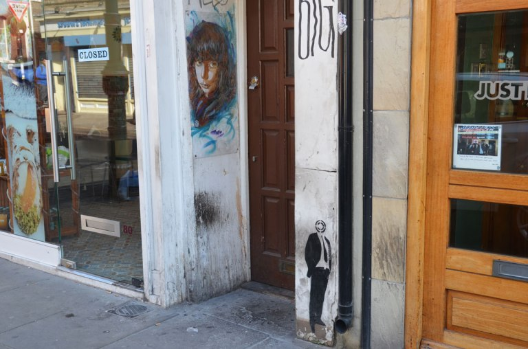 a very small black stencil of a man with a target as a head, standing on a wall, with feet at sidewalk level . Near him is a woman's face painted on the wall of a doorway