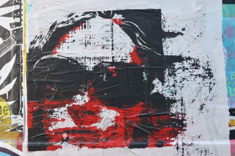 paste up of a woman's head, black sunglasses, with some red details and highlights on her face