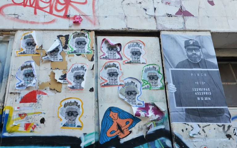 many identical paste ups of Queen Elizabeth's head, outlined in different colours, pasted on a wall,