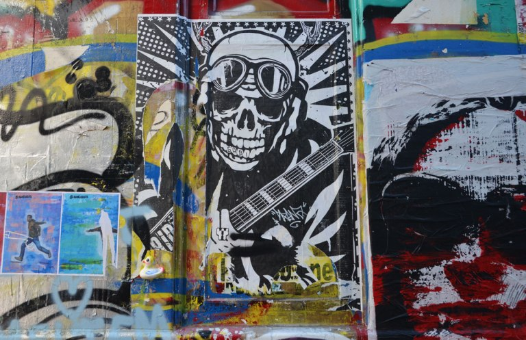 street art of a man with skull face, helmet and googles on his forehead, ammo belt across his chest.