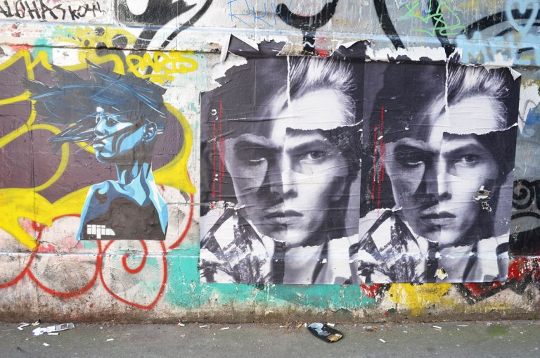 three graffiti faces on a wall, one woman in profile painted in blues and two identical black and white paste ups of a young man
