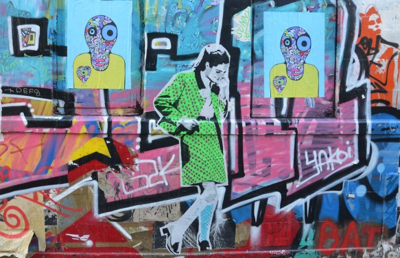 street art and graffiti on a wall, a woman in a green skirt suit and some creature's heads