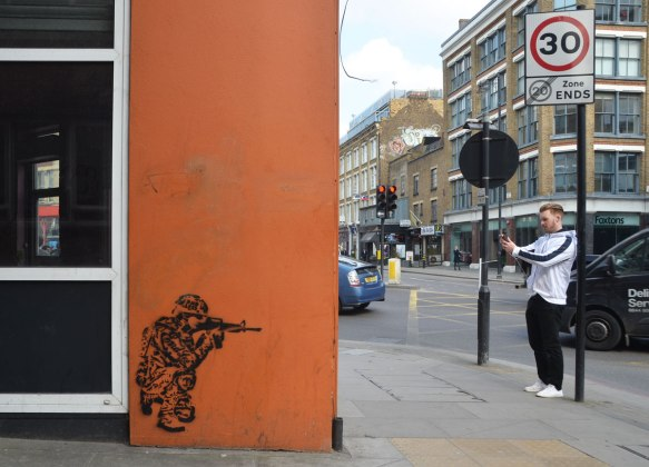 street art piece of a person squatting beside a building, shooting an automatic weapon towards the edge of the building. A young man is taking a picture with his phone on the other side of the building.