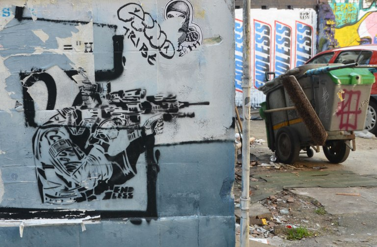 street art piece of a person squatting beside a building, shooting an automatic weapon towards the edge of the building. A trash can and car are beside the building