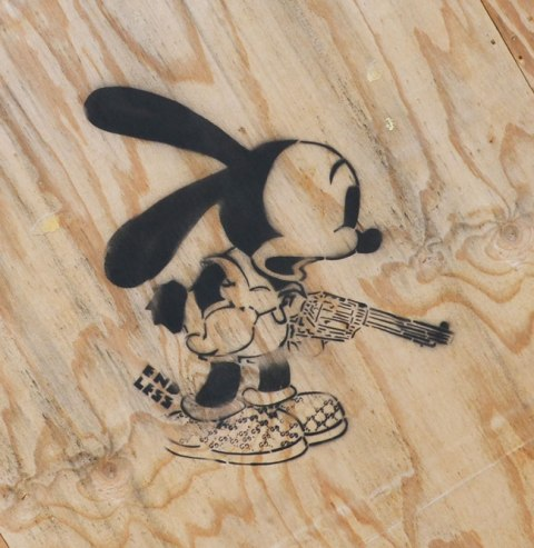 black stencil on wood of mickey mouse holding a revolver