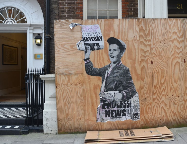 on wood construction hoardings, a paste up by endless of a newspaper boy holding up a newspaper