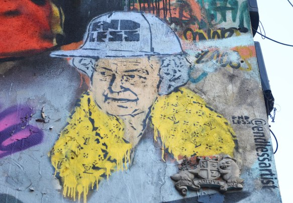 street art piece of head of Queen Elizabeth, wearing a hard hat with endless written on it, as well as a yellow scarf with Yves Saint Laurent logo on it.