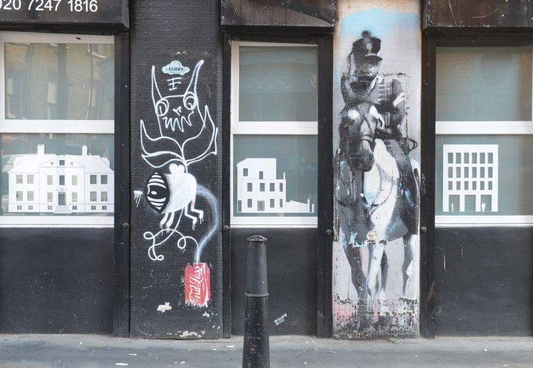 two vertical street art pieces on a black building, with windows on either side of them. one is a soldier on a horse and the other is a white drawing by endless