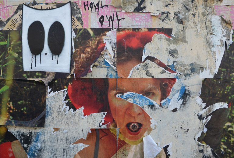 street art, collage woman's face with an eyeball in her mouth, scrawled letters of Howl Owl and a white rectangle with two black ovals,