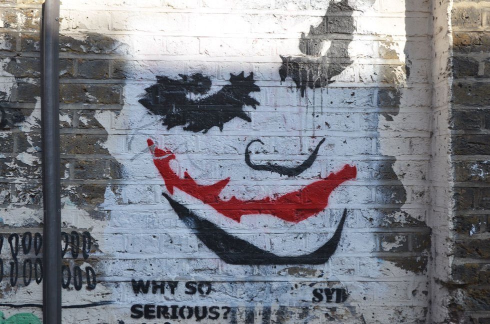 street art painting of the joker's face up close, bright red mouth, other features in black on white, with the words, Why so serious? bySyd