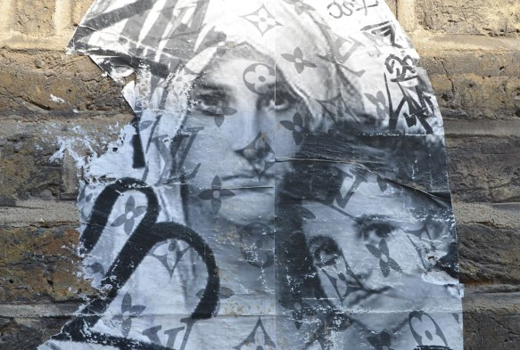 detail of a paste up of a woman in a head scarf made of fabric with the Yves Saint Laurent logo all over it and a child, in grey tones