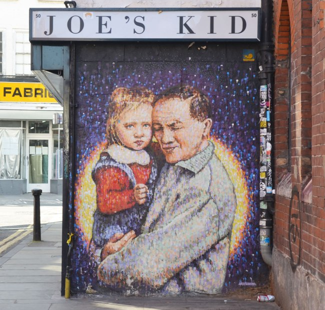 A man hugging a young girl, Joe's Kid is the title,