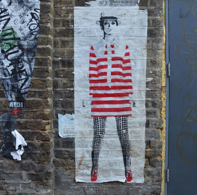 large paste up of woman standing, looks like Liza Minelli in red and white striped long top and black leggings, red shoes, on a brick wall